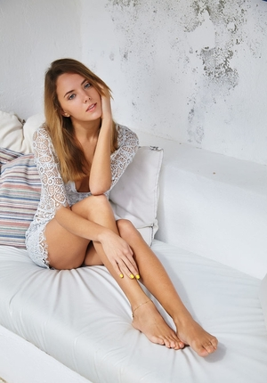 Young-looking model with beautiful face poses at the photo shoot on the snow-white sofa