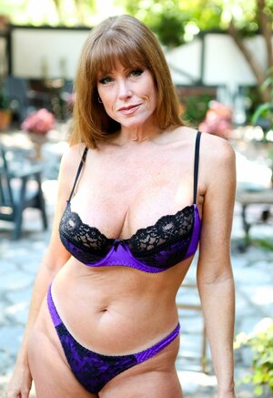 Aged cougar Darla Crane teases with busty body in sexy lingerie outside